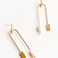 Apricot: Post back gold earrings with curved arc featuring one cream color beaded end and one square gold end.