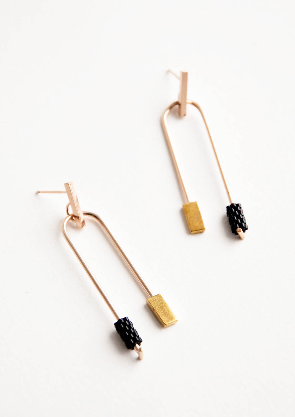 Onyx: Post back gold earrings with curved arc featuring one black beaded end and one square gold end.