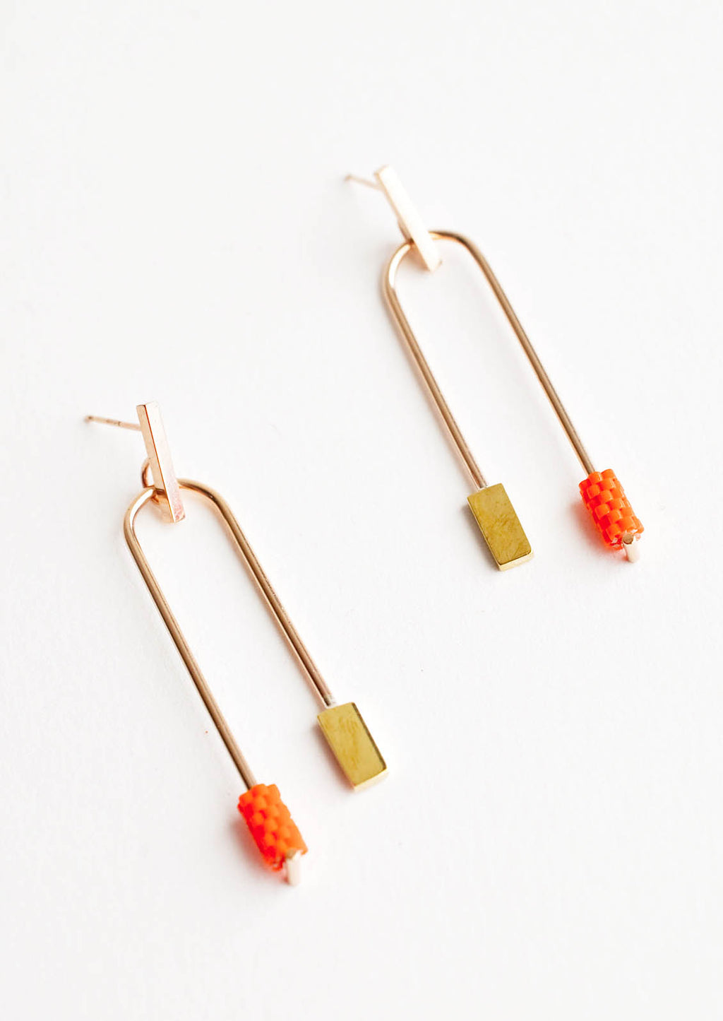 Orange: Post back gold earrings with curved arc featuring one orange beaded end and one square gold end.