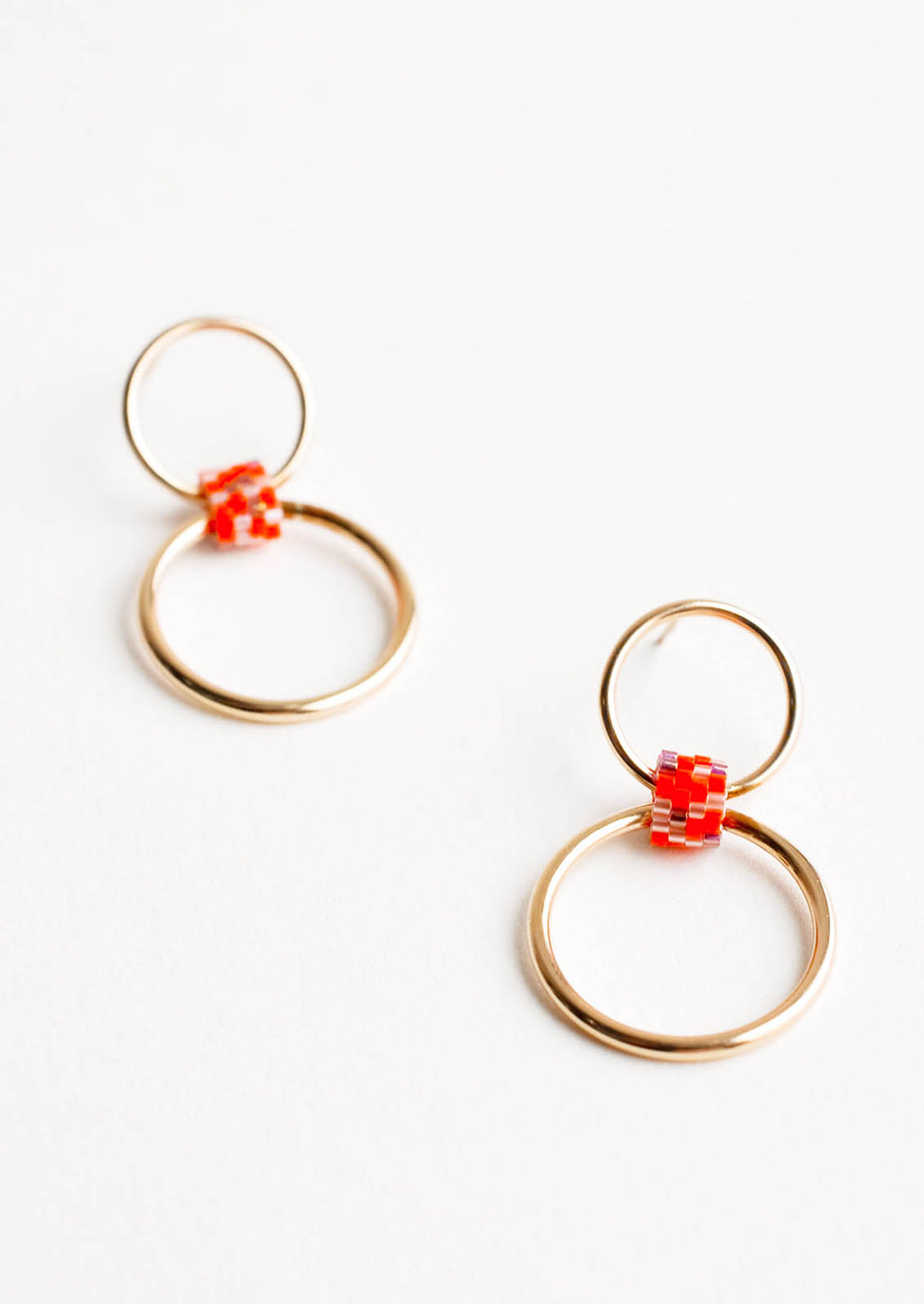 Orange Multi: Post back earrings of one small gold hoop and one larger gold hoop connected by a loop of orange glass beads.