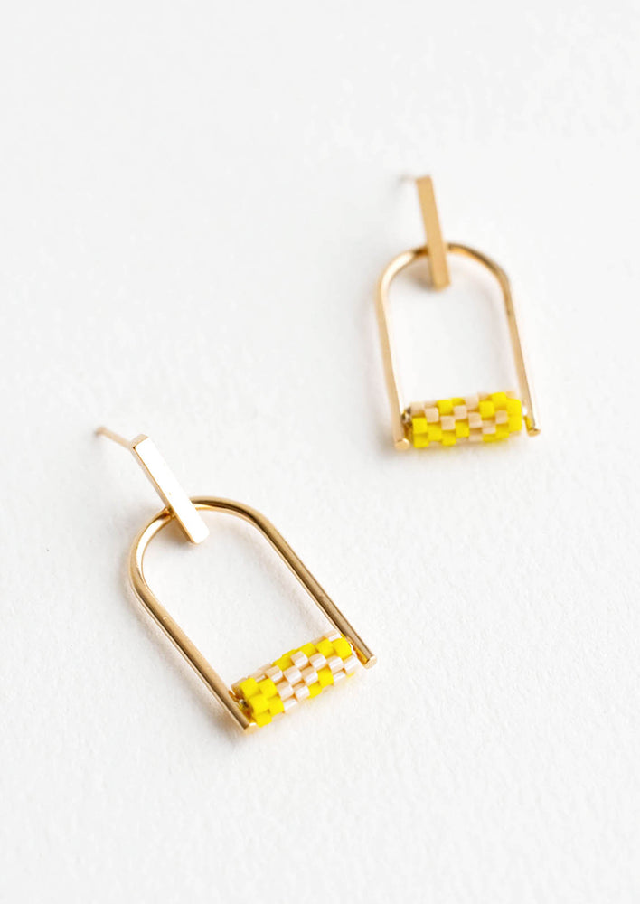 2: Arced gold post back earrings with yellow beads closing off the arc.