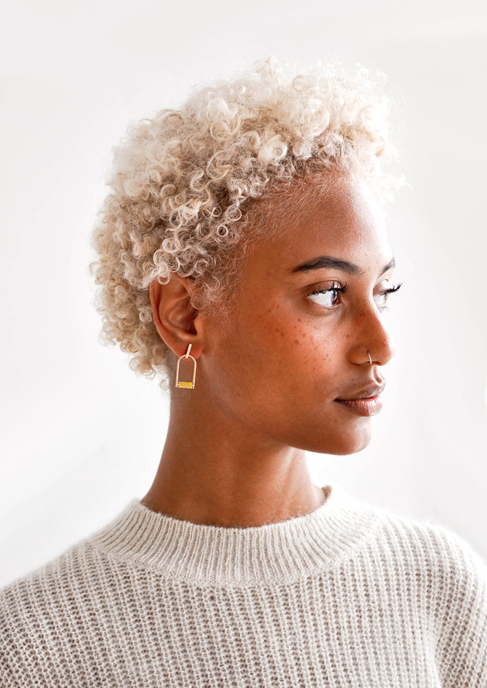 3: Model wears arced gold earrings with yellow beads and a cream colored sweater.