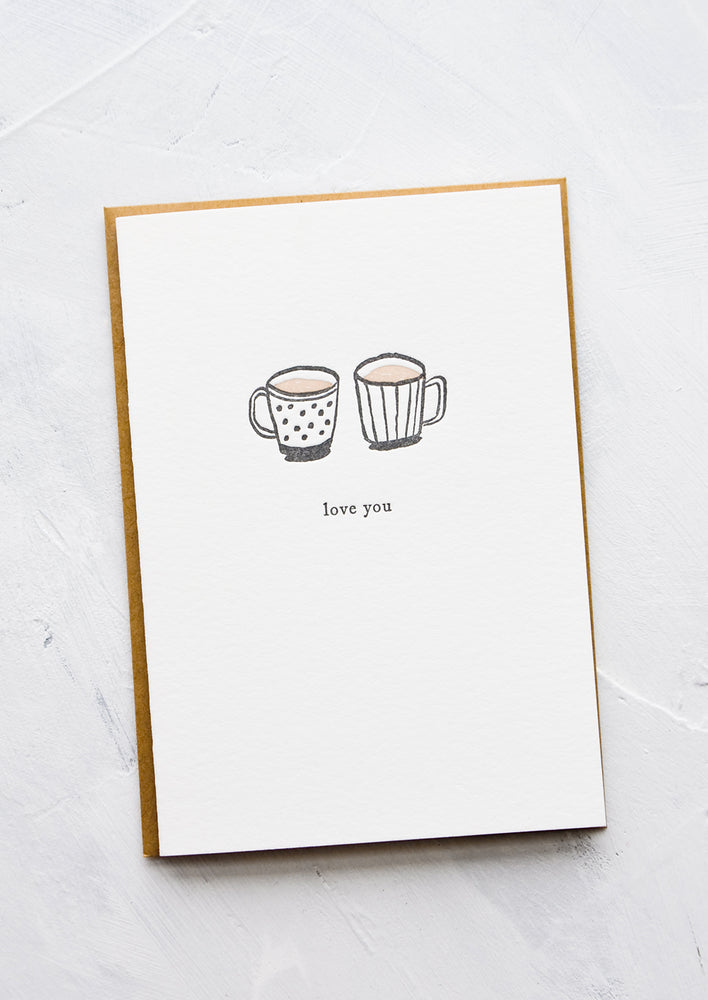 "1: A letterpress printed greeting card with an image of two coffee mugs side by side, text below image reads ""love you""."