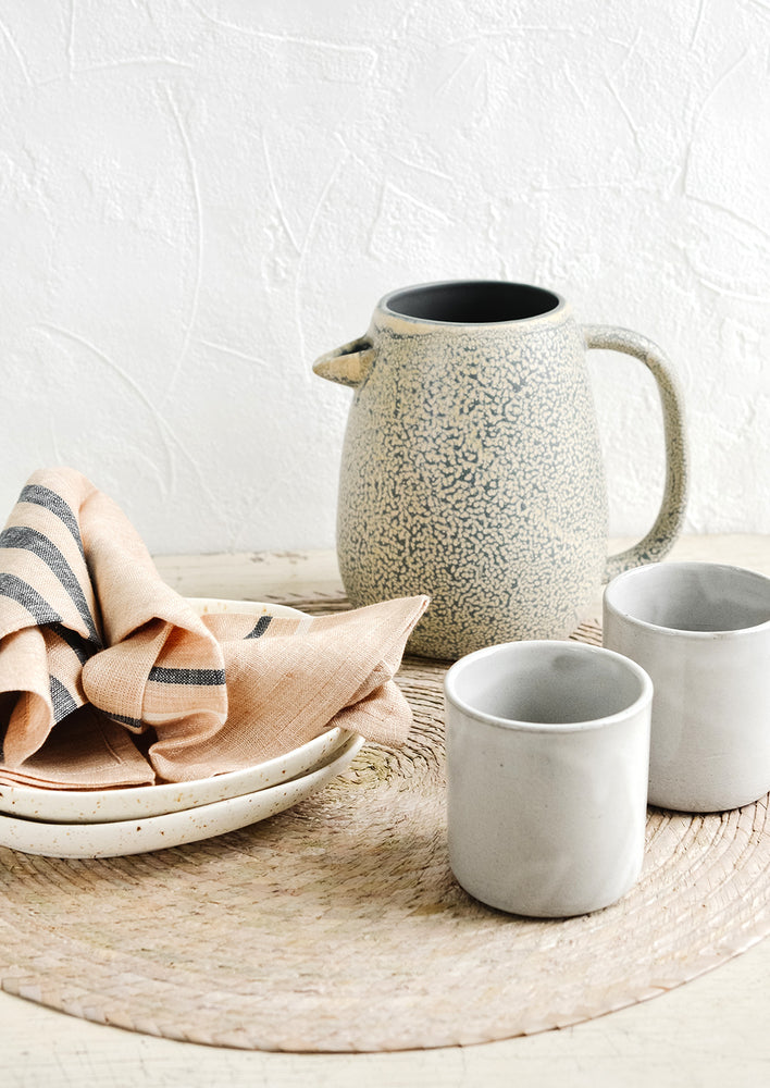 2: An arrangement of assorted tableware in warm pastel hues.