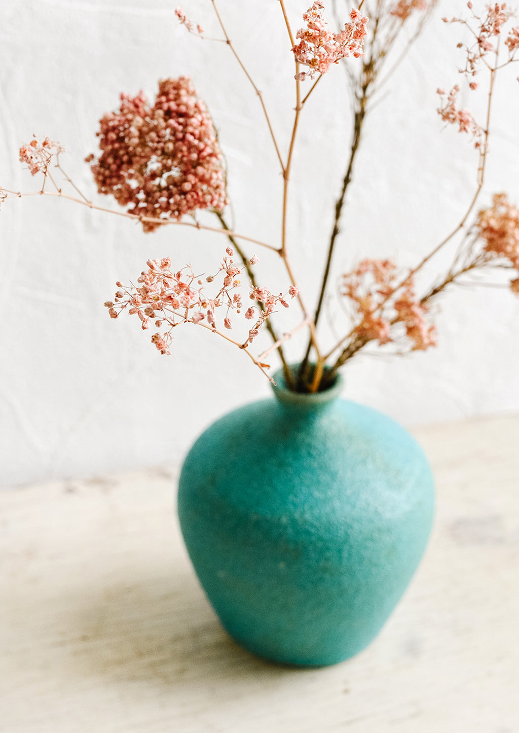 2: A textured turquoise ceramic vase with dried pink flowers inside.