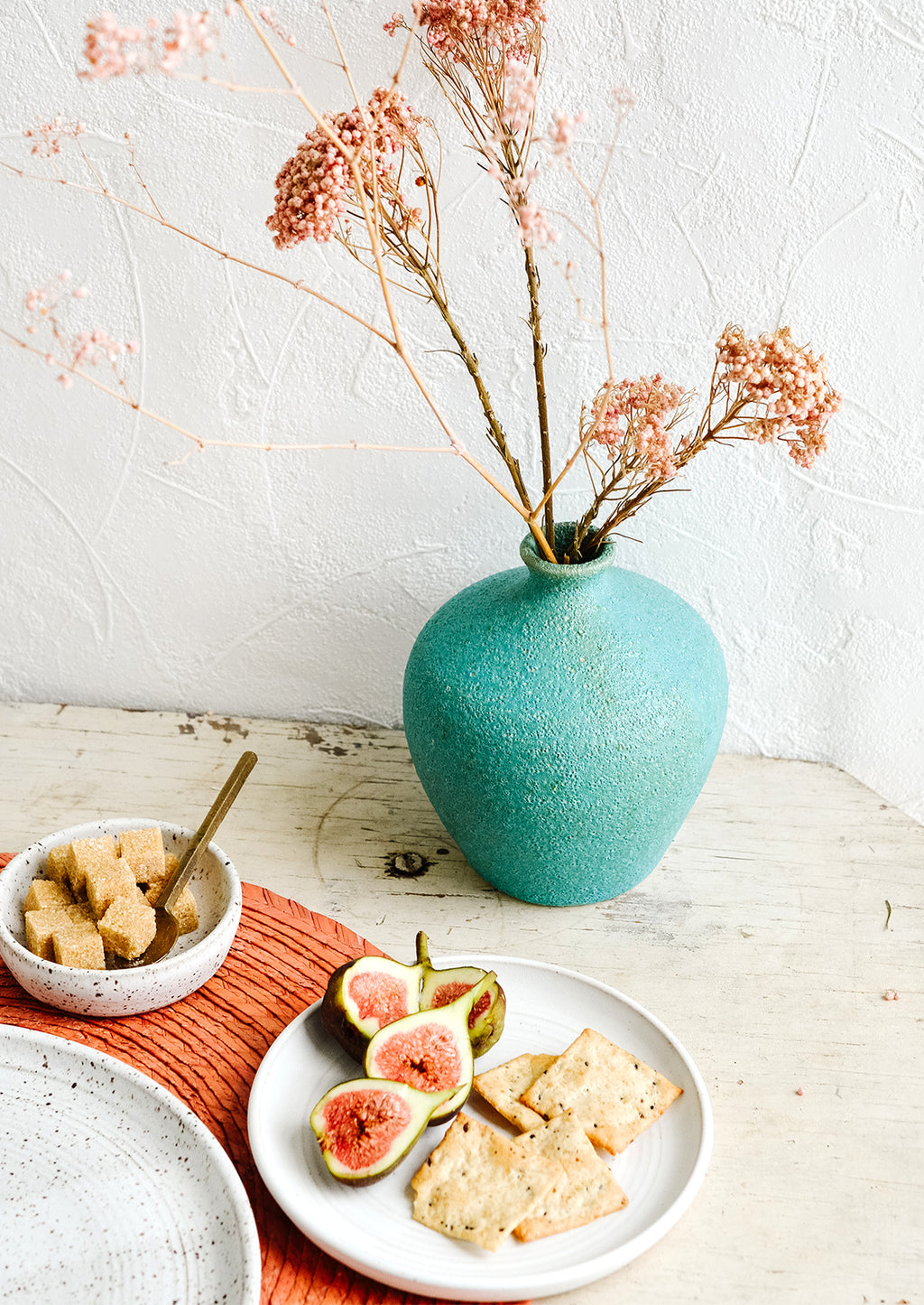 3: A turquoise ceramic vase amidst a breakfast tabletop scene.