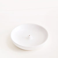2: A simple white dish with a small hold at the center for holding incense.