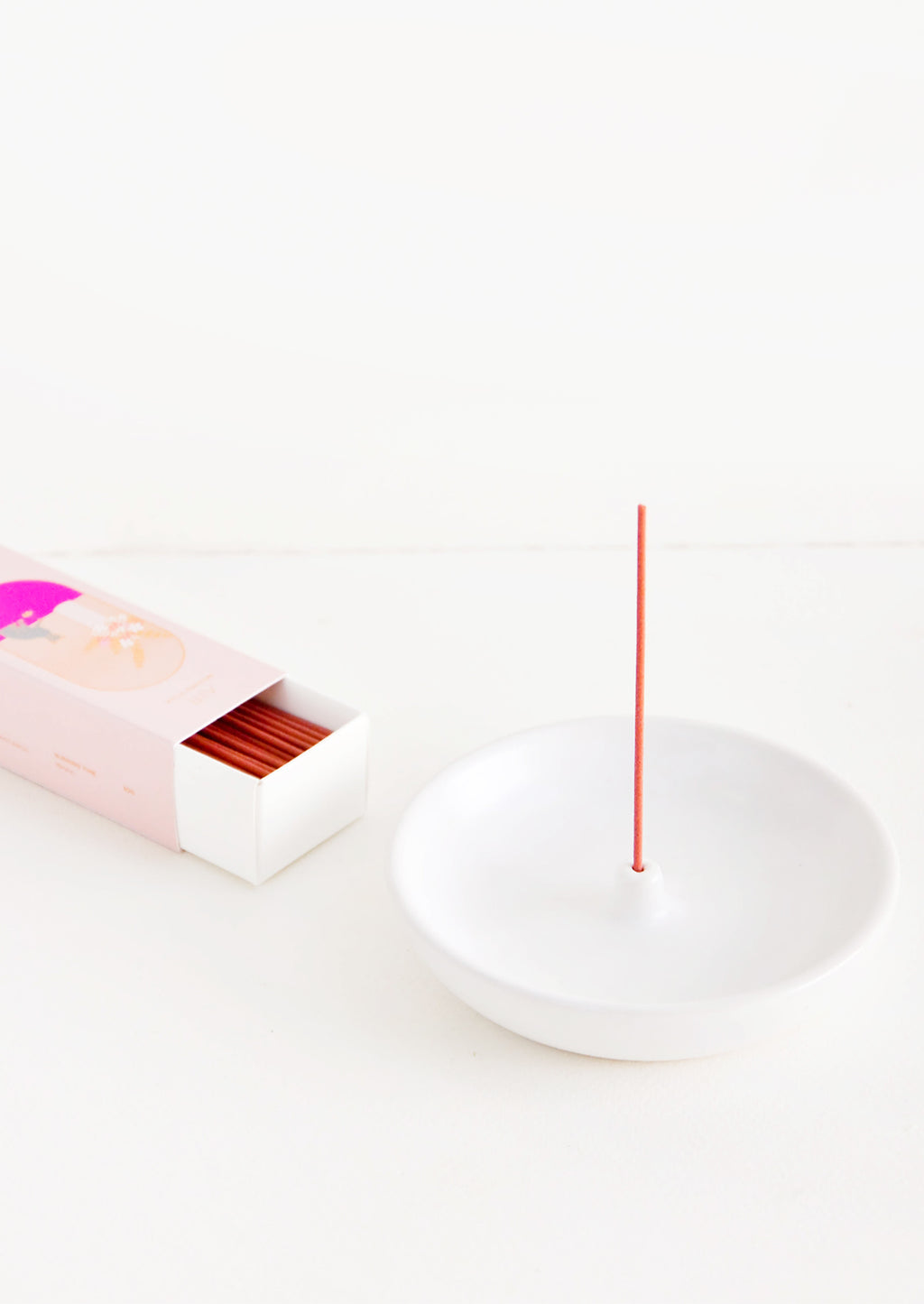 1: A simple white curved ceramic incense holder with a pink stick of incense and a pink box of incense next to it.