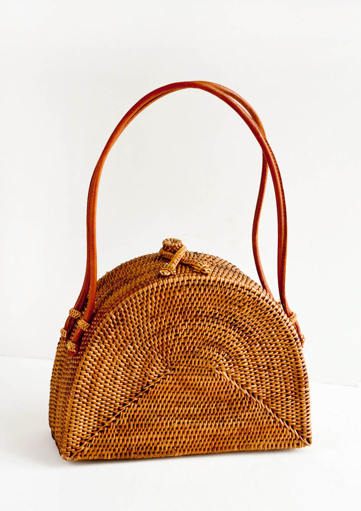 1: Half-oval shaped, structured handbag made from smoked rattan. Tanned leather carrying handles.