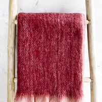 1: Plush, fuzzy blanket in wine red color with pale pink trim, displayed on ladder