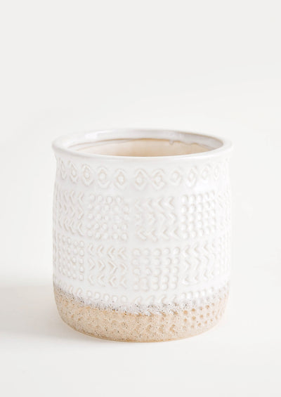 Round ceramic planter with glossy white glaze and natural clay exposed at bottom, allover textured tribal pattern