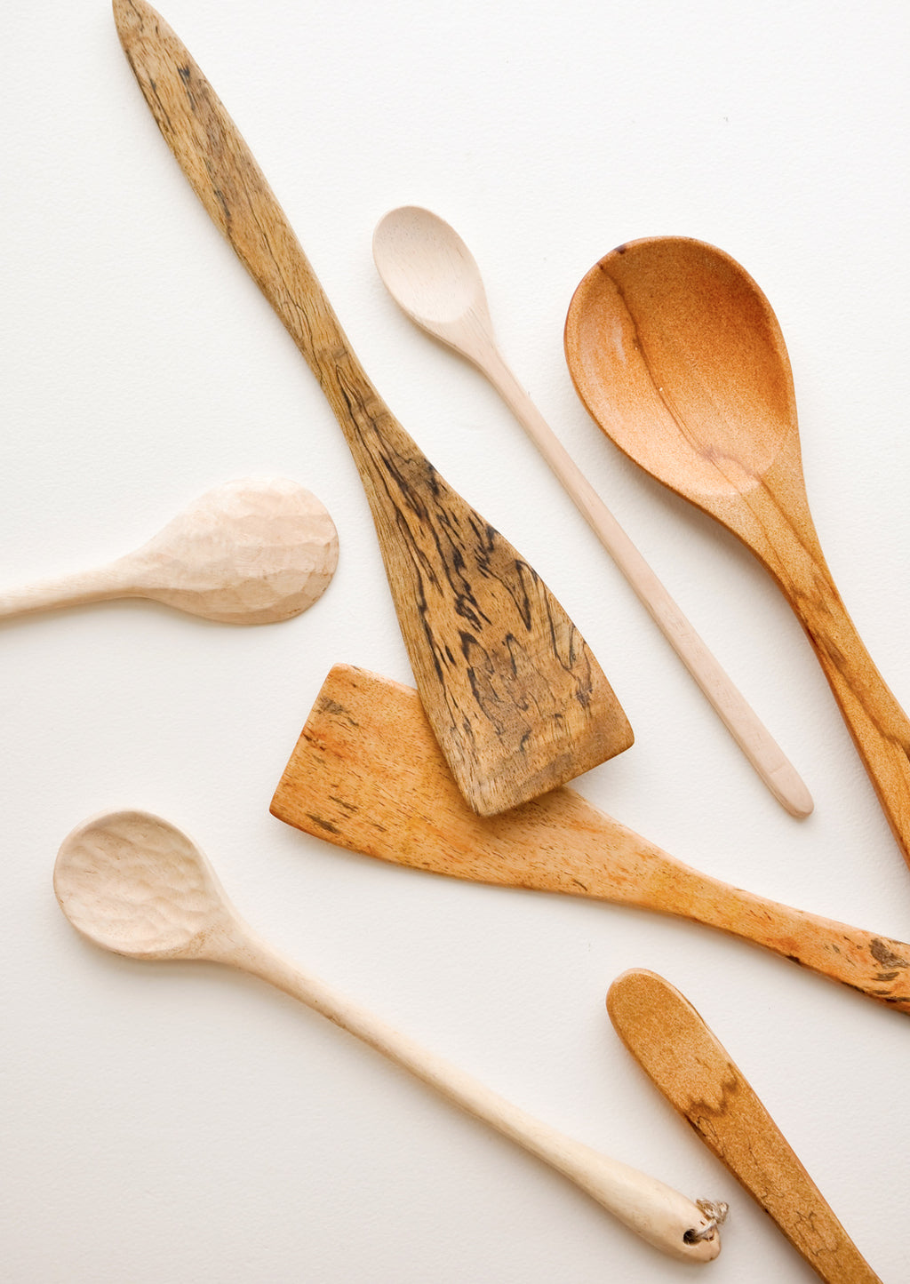 1: Wooden spoons of different colors, shapes, and sizes displayed in a haphazard d fashion.