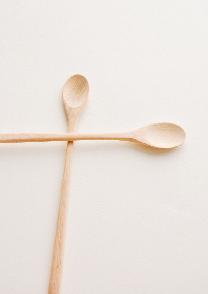 Two pale wood spoons with long thin handles and proportionally small, oval heads.