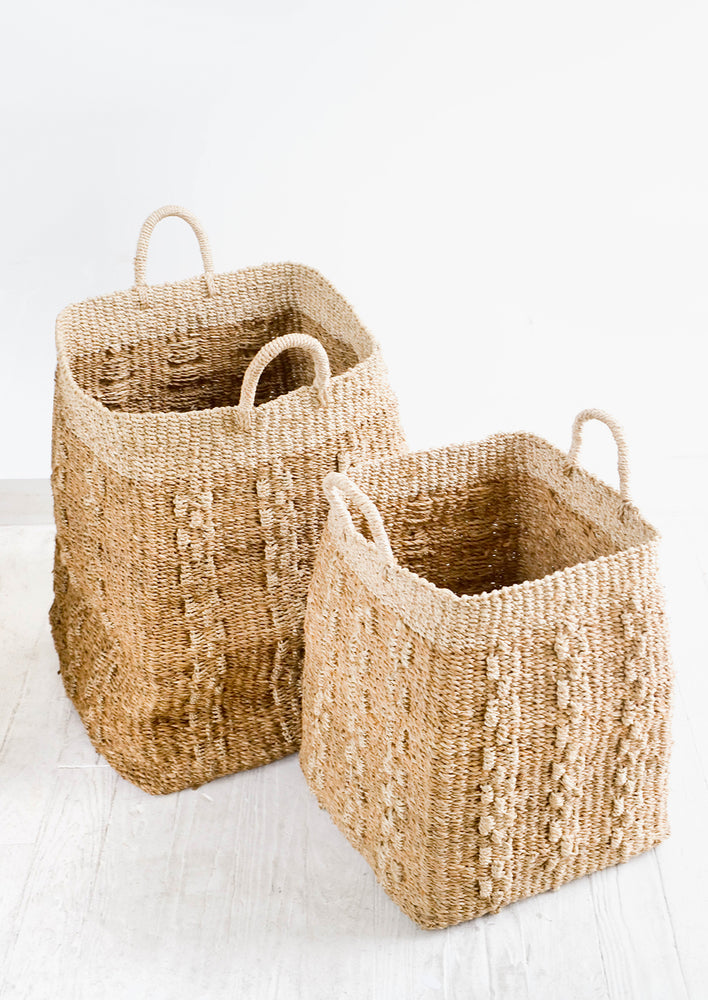 2: Two incremental sizes of tall, tan colored square storage basket made from banana leaf fiber with decorative woven pattern.