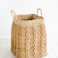 1: Tall, tan colored square storage basket made from banana leaf fiber with decorative woven pattern.
