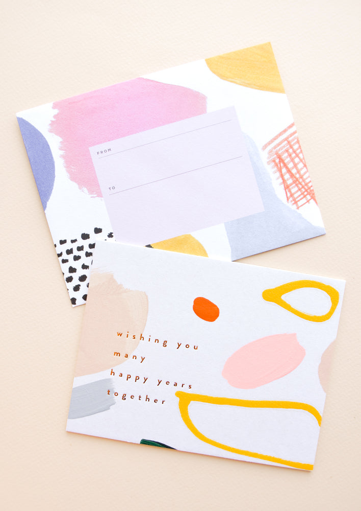 "1: Greeting card with colorful abstract shapes and ""Wishing you many happy years together"" text. Shown with matching envelope."