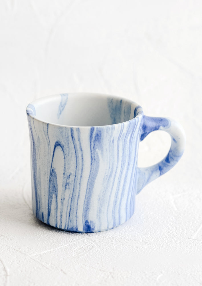 1: A ceramic mug in white with marbleized pattern in blue.