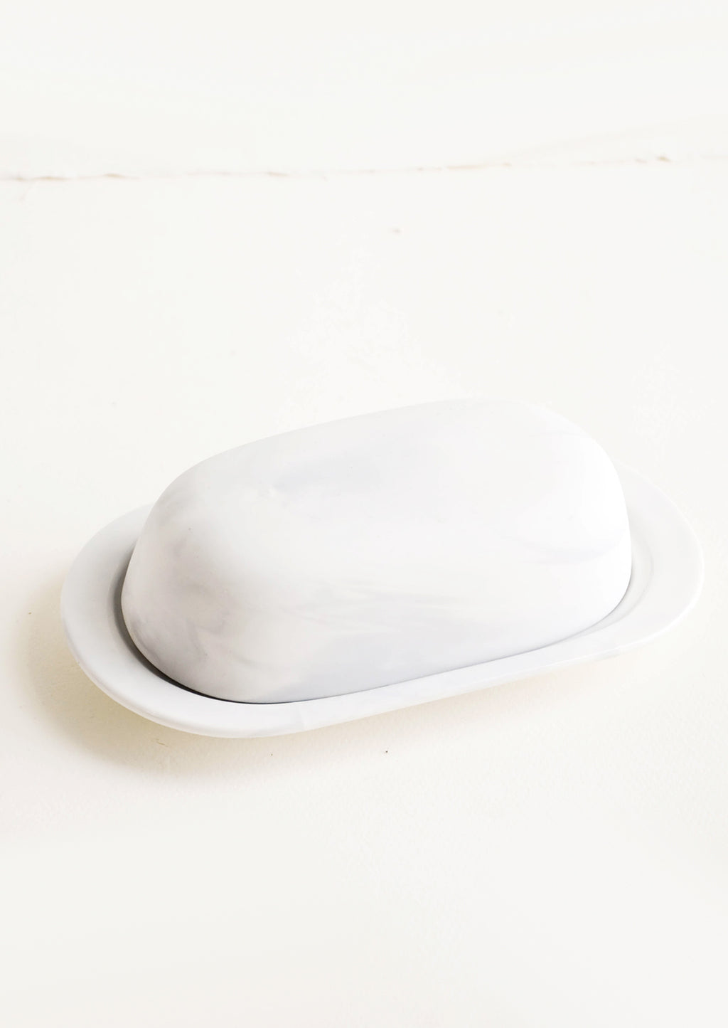 1: Oval shaped butter dish with curved dome lid, matte white ceramic with pale grey marbleized effect