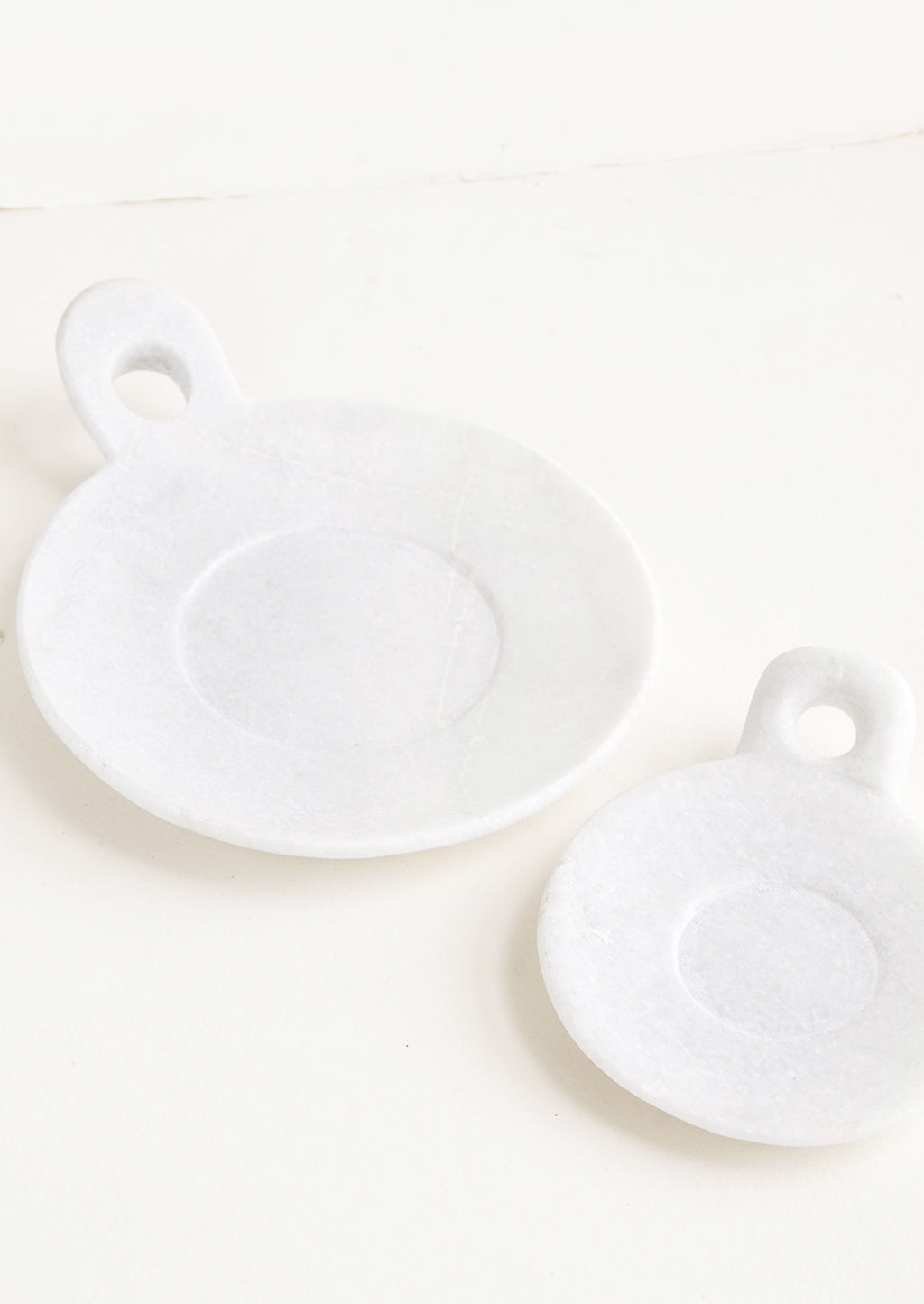 2: Round marble dishes with circular cutout side handle and circular inset at center