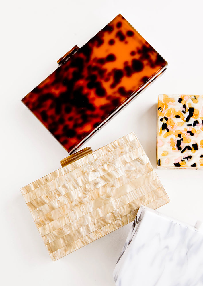 2: Aerial shot of rectangular, box-shaped clutch handbags in various resins