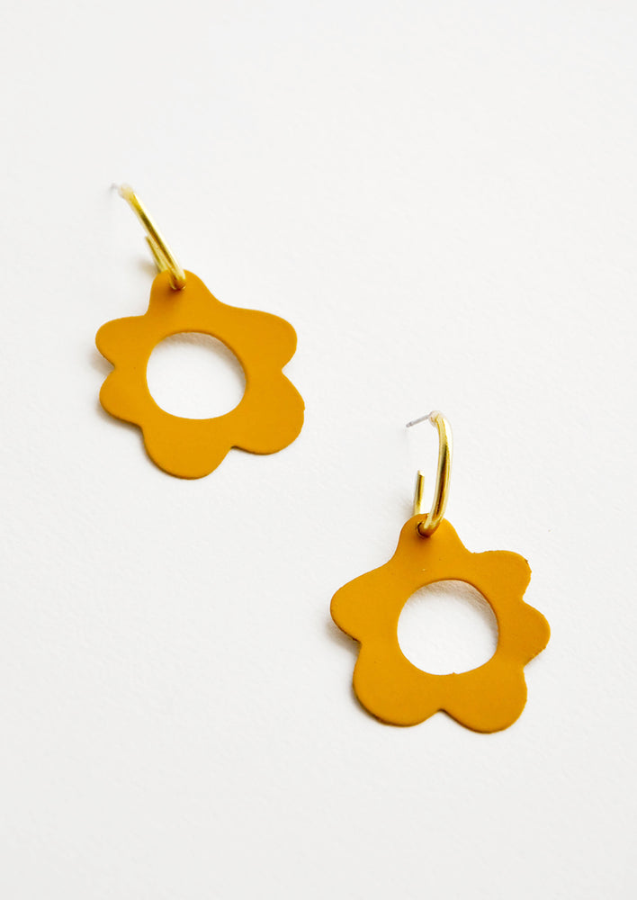 Saffron: Mustard yellow flower shaped earrings with circular cutouts on small brass open hoops.