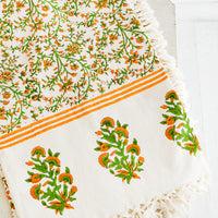 1: Block printed cotton tablecloth with orange and green floral pattern and tasseled edges