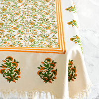 2: Block printed cotton tablecloth with orange and green floral pattern and tasseled edges, displayed on a table