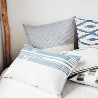 2: Assorted throw pillows in shades of blue and pink scattered atop a bed