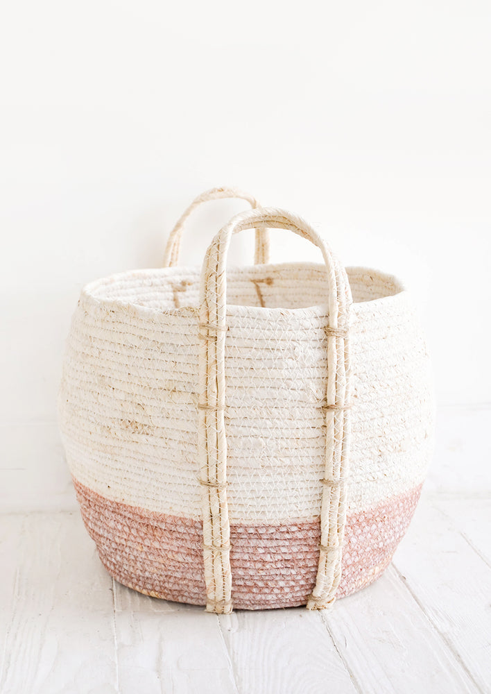 Dusty Rose / Low [Large]: Round storage basket made from natural maize fiber, fiber handles attached at sides, band of contrasting pink color along bottom.