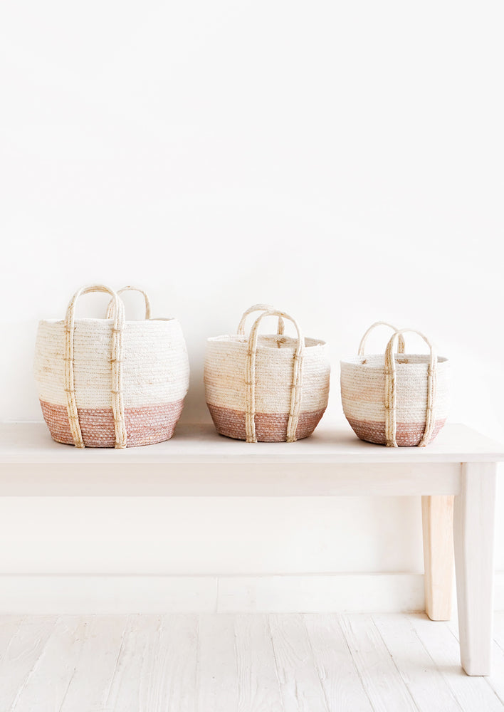 Dusty Rose / Low [Small]: Line up of three round storage baskets in incremental sizes, handles attached at sides, band of contrasting pink color along bottom.