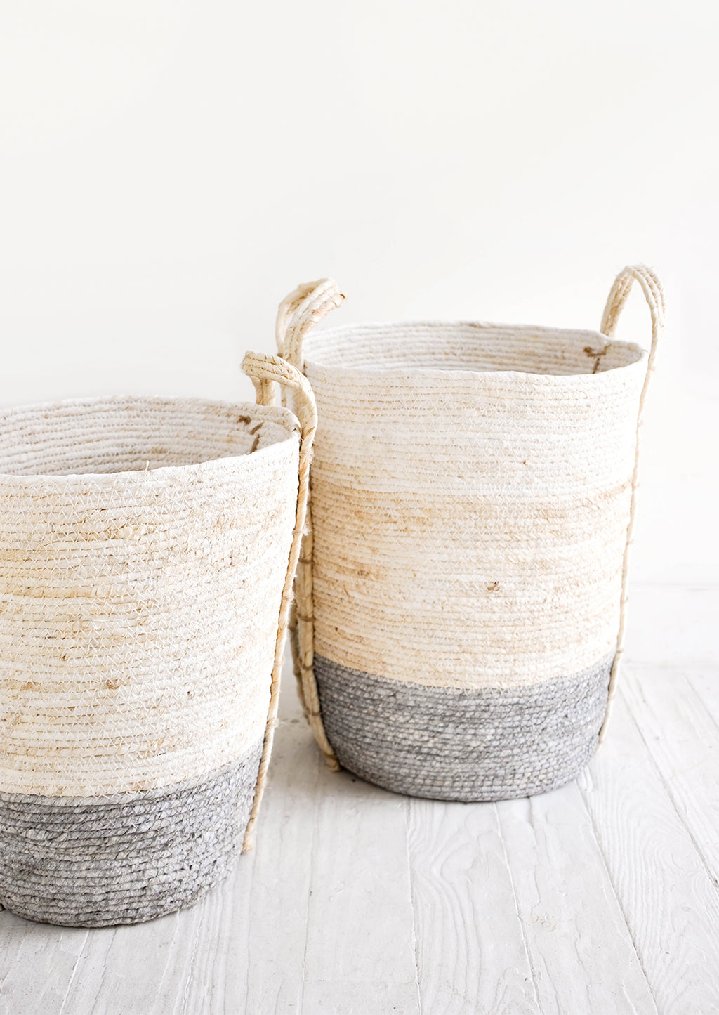 Slate / Tall [Small]: Tall, round storage baskets made from natural maize fiber, fiber handles attached at sides, band of contrasting grey color along bottom.