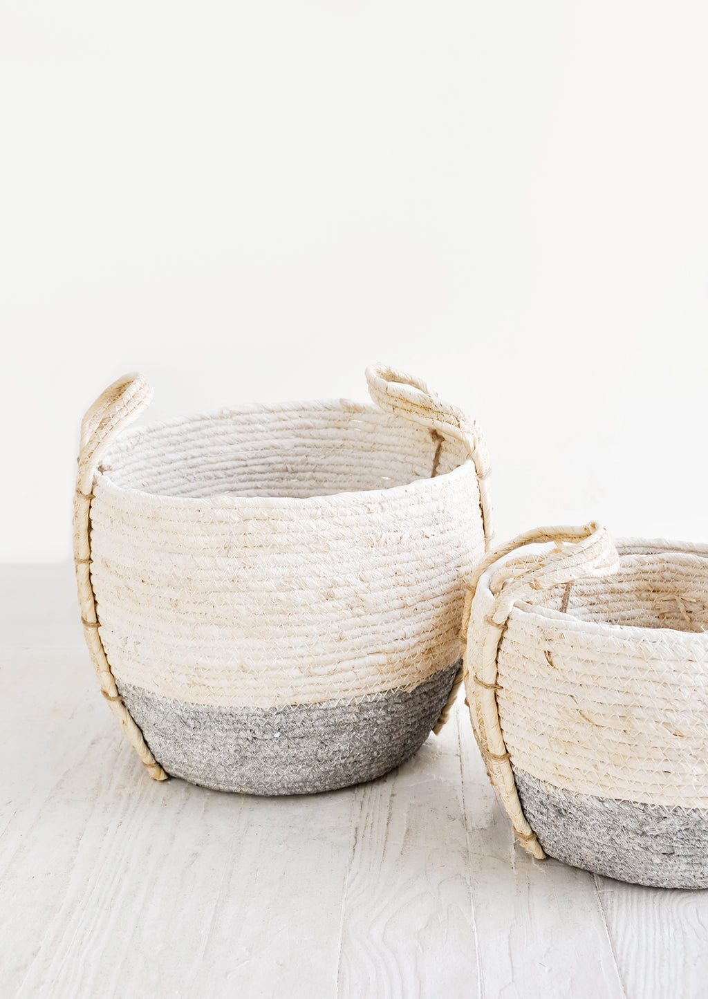 Slate / Low [Small]: Small, round storage baskets made from natural maize fiber, fiber handles attached at sides, band of contrasting grey color along bottom.
