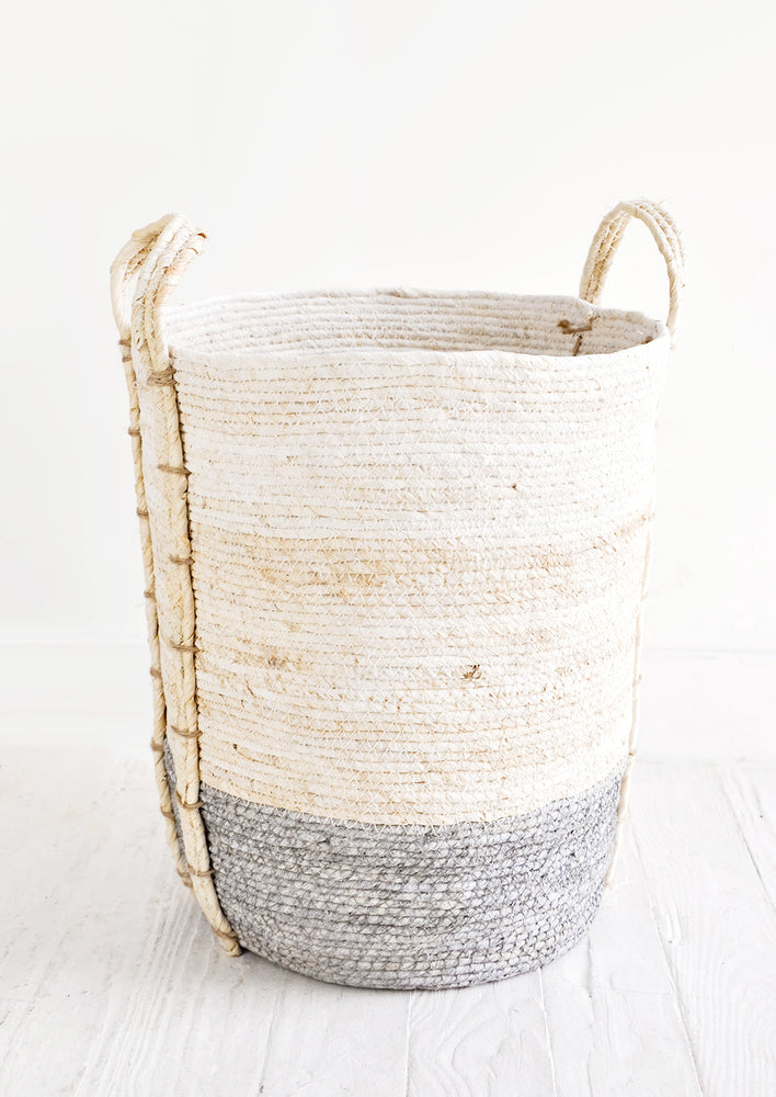 Slate / Tall [Large]: Round, tall storage basket made from natural maize fiber, fiber handles attached at sides, band of contrasting grey color along bottom.
