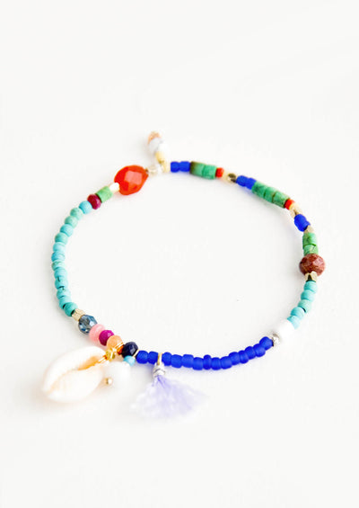 Beaded bracelet with a mix of gemstone & matte glass beads, shell & tassel charm detail
