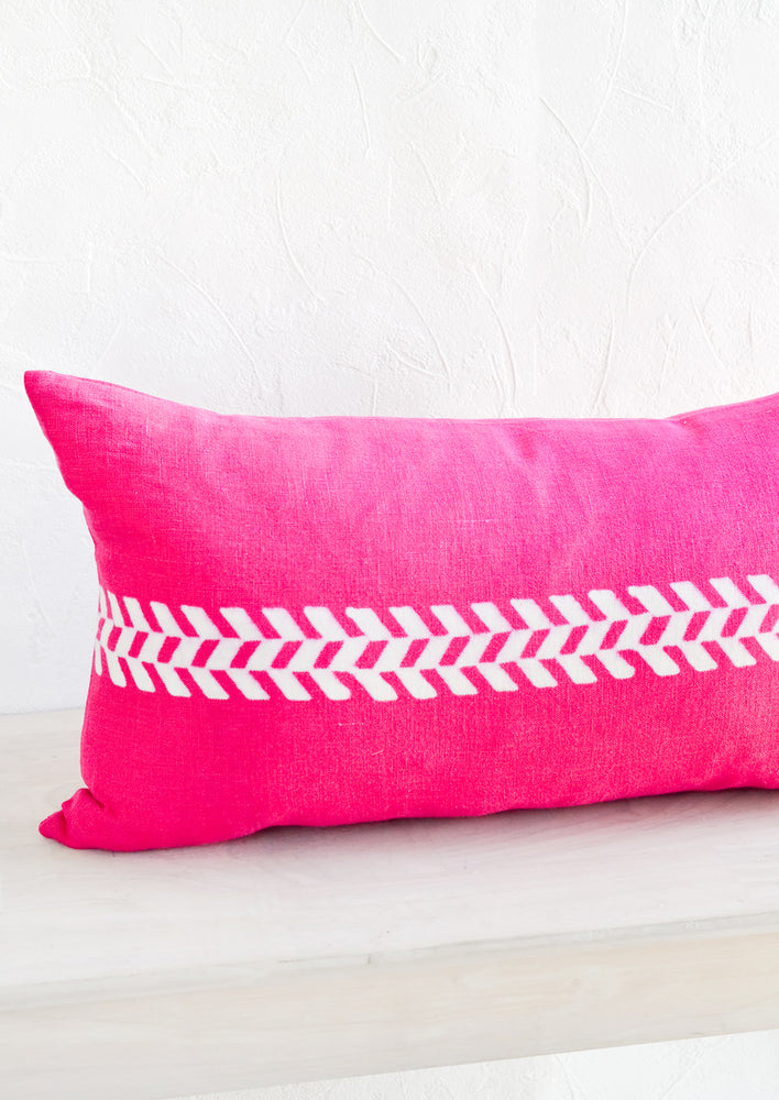 A lumbar throw pillow in bright pink linen with white herringbone block print detail across middle.