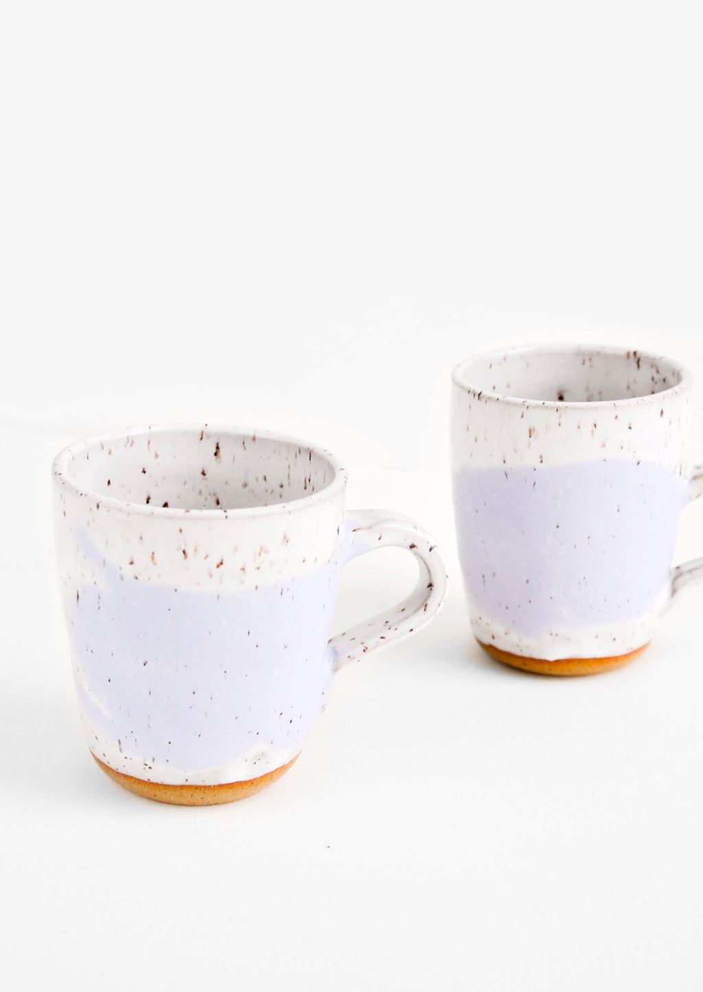 White / Wisteria: Two ceramic mugs in white and purple with brown speckles.