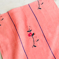 2: A pink linen napkin with a minimal floral block print design and two vertical blue stripes.