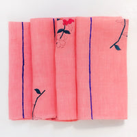 1: A folded pink linen napkin with block printed flowers and stripes.