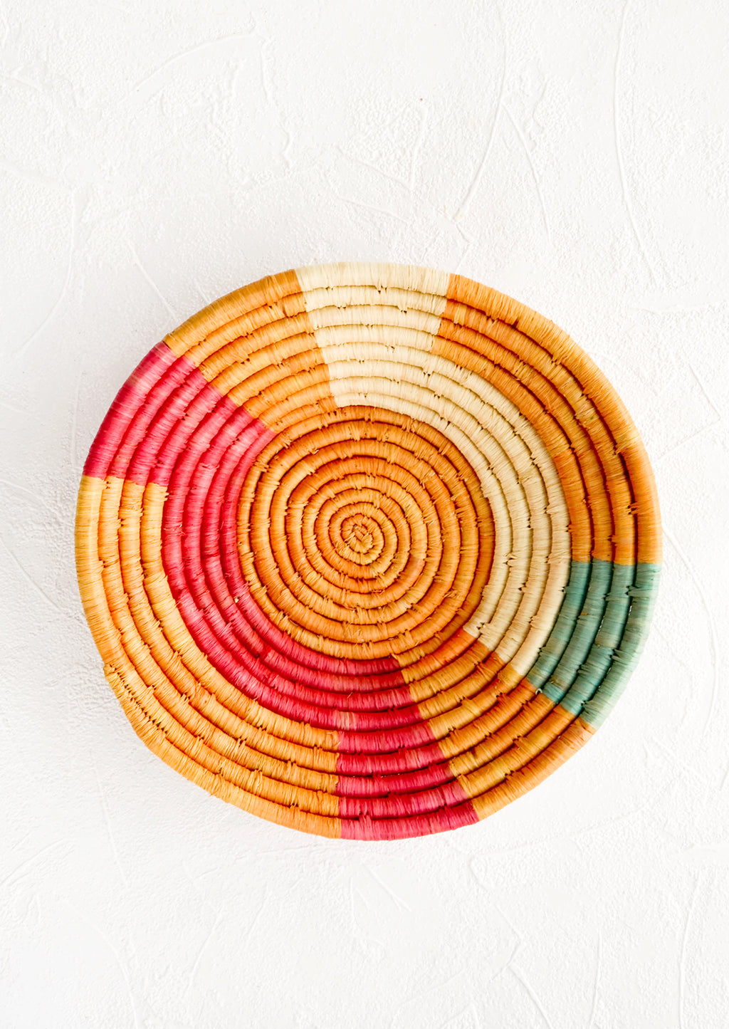 1: Woven raffia bowl in mustard, pink, natural and turquoise geometric pattern