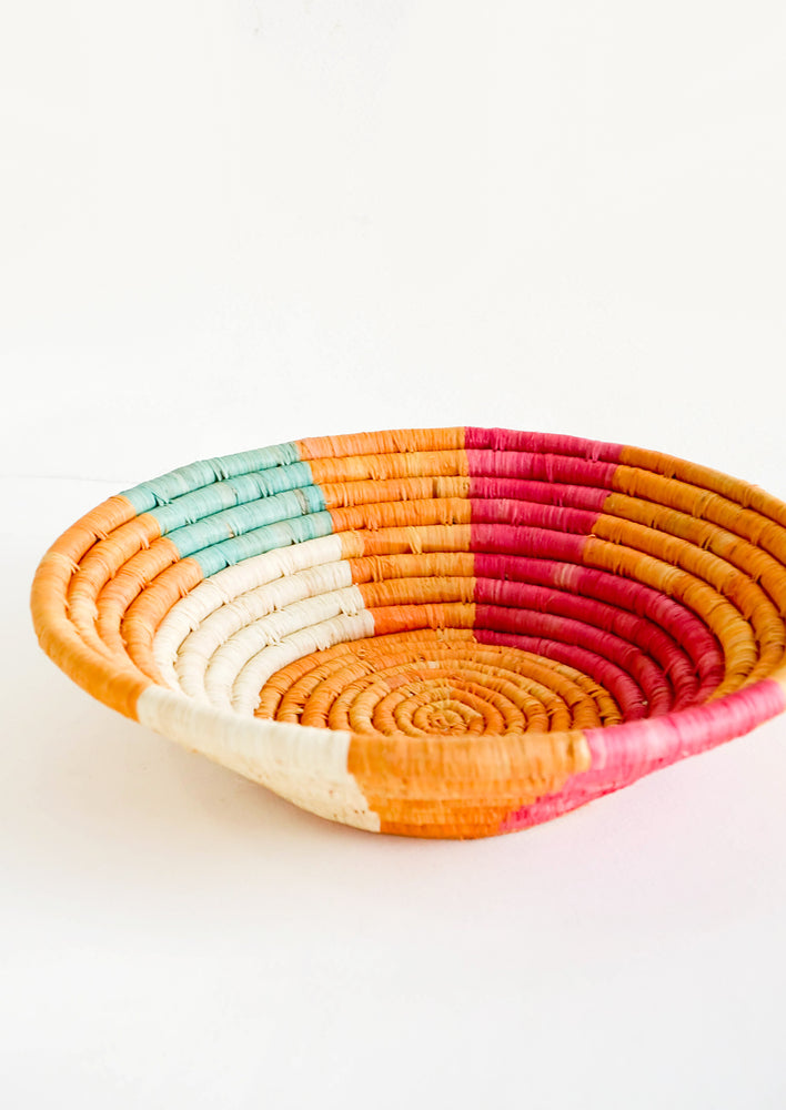2: Shallow raffia bowl in mustard, pink, natural and turquoise geometric pattern