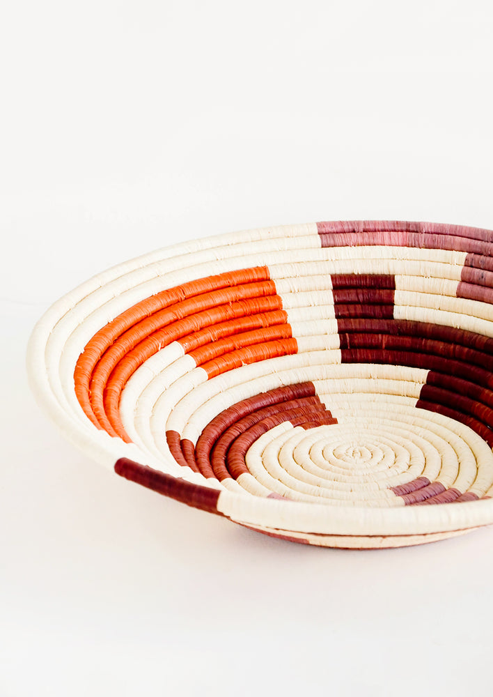 2: Shallow woven raffia bowl with maze print in wine, orange and mauve