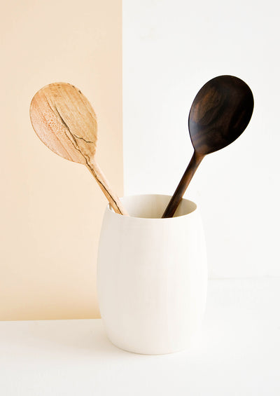 Two wooden spoons displayed in a very pale wooden vase-like container.