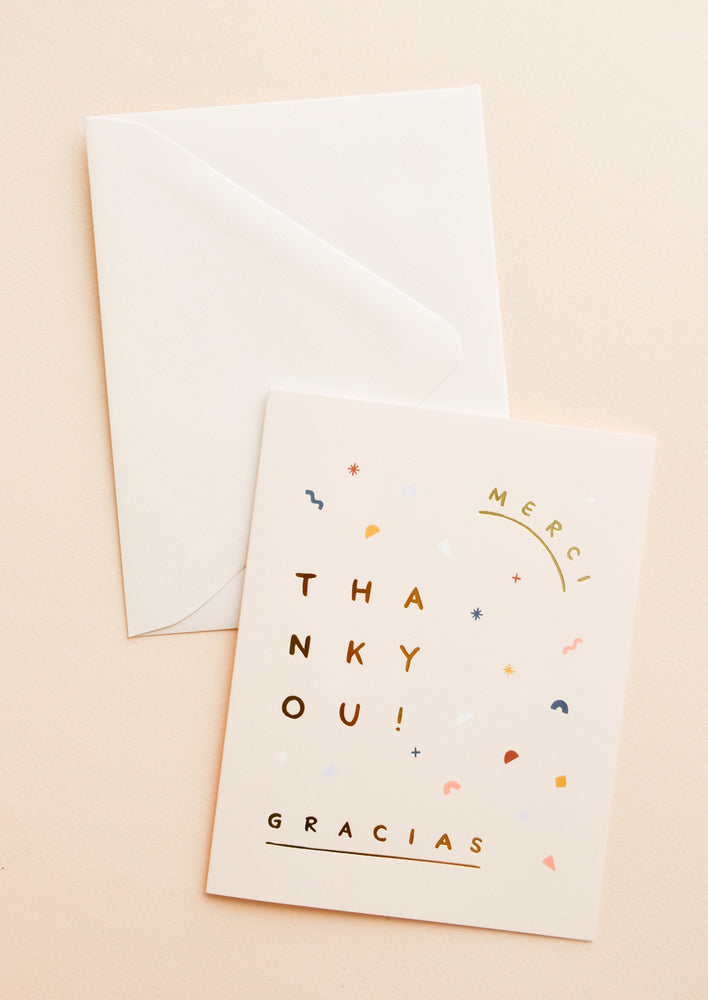 "1: Pale pink notecard with abstract confetti decoration and the words ""Merci"", ""Gracias"" and ""Thank You"", and white envelope."