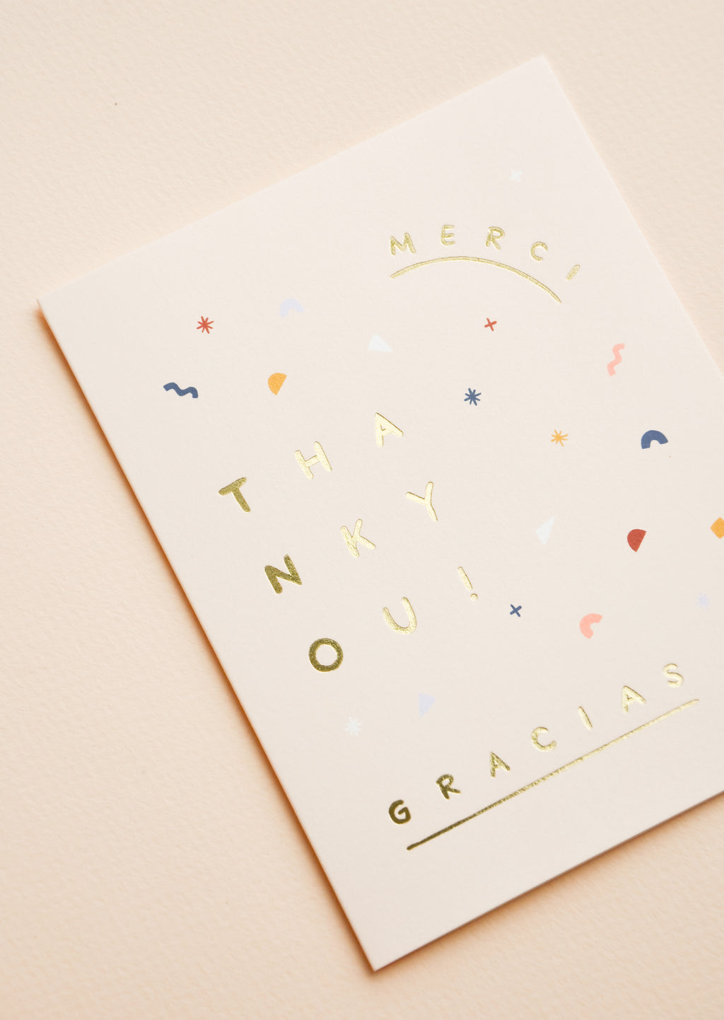 "2: Close up of pale pink notecard with abstract confetti decoration and the words ""Merci"", ""Gracias"" and ""Thank You""."