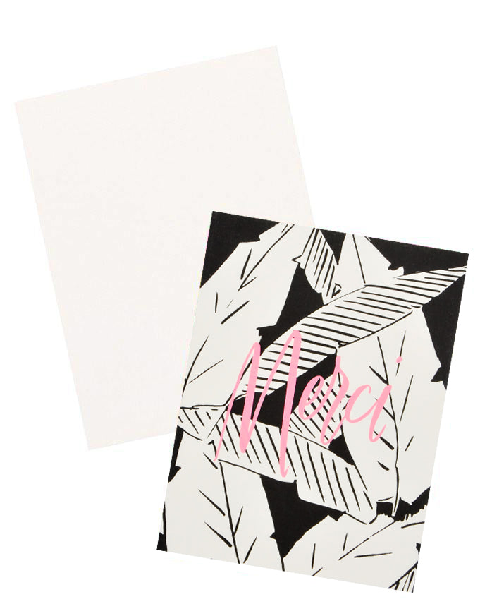 "3: Notecard with black and white palm leaves decoration and the word ""Merci"" in pink, and white envelope."