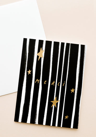 "A black and white horizontal striped greeting card with a sparse array of gold stars and the word ""merci"" in gold."