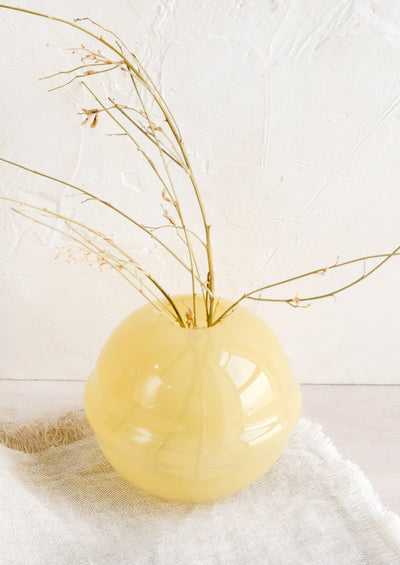 A spherical glass vase in translucent yellow.