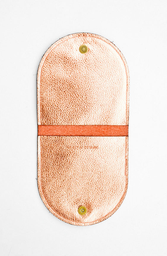3: A metallic copper half-oval wallet opened to expose the interior pockets, snaps, and brand logo.