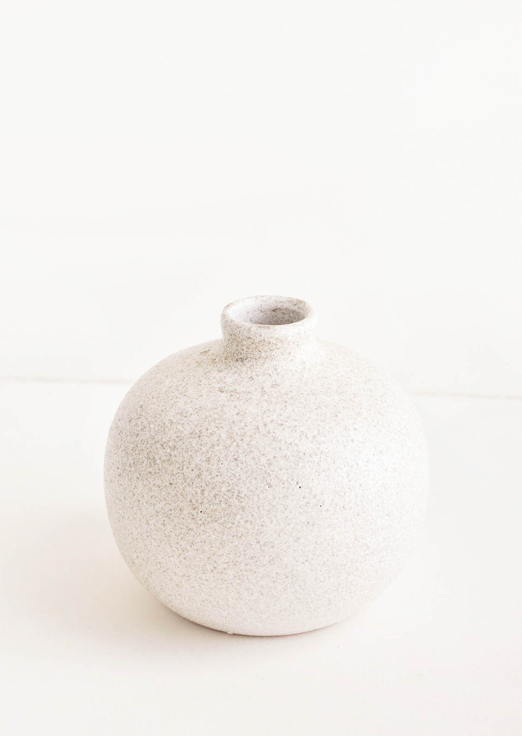 Short [$40.00]: Ceramic vase with bulbous base and narrow opening, in textured light grey glaze