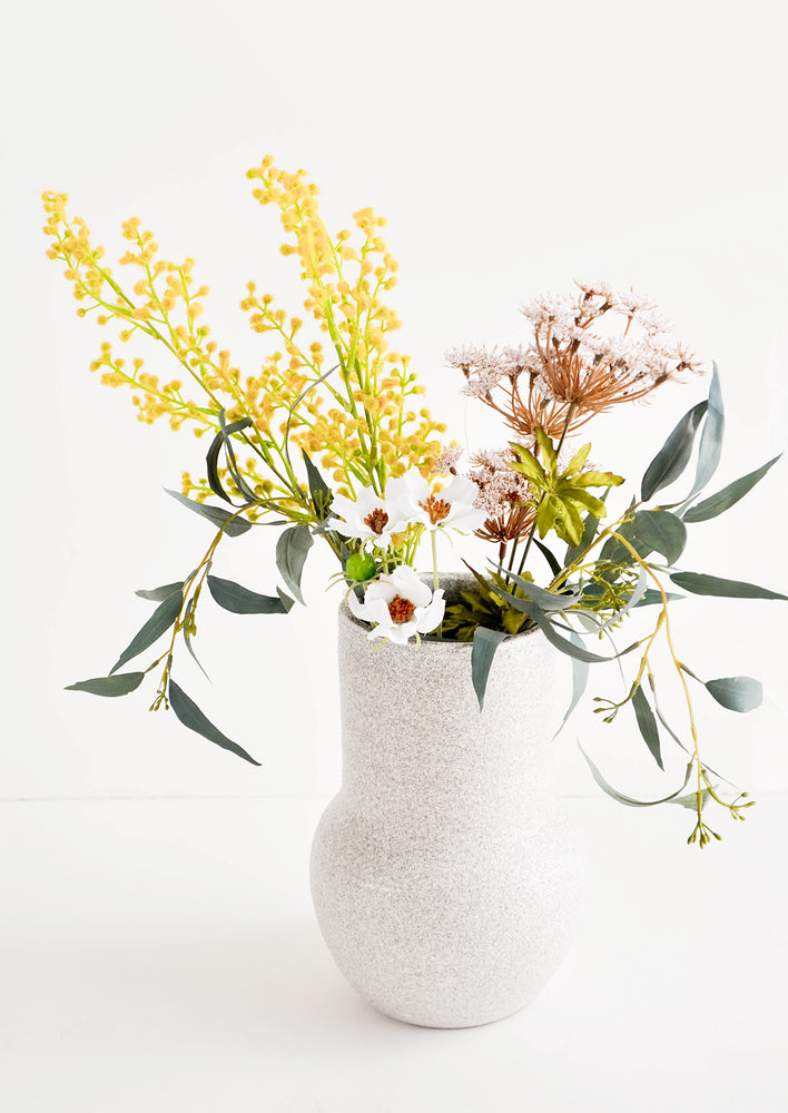 Tall ceramic vase in textured light grey glaze, pictured with floral bouquet